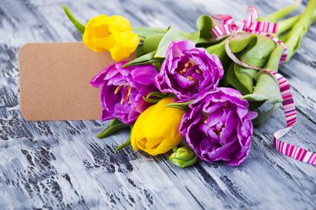 Beautiful purple and yellow tulips  with a card on wooden background photo