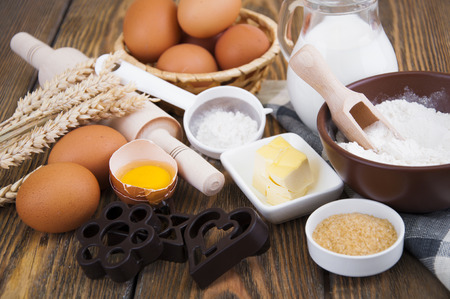 Baking ingredients - eggs, flour,milk,sugar and butter on a wooden background photo