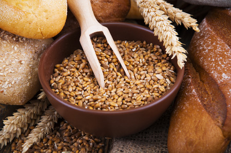 wheat: Wheat in a plate with different bread on a wooden table Stock Photo