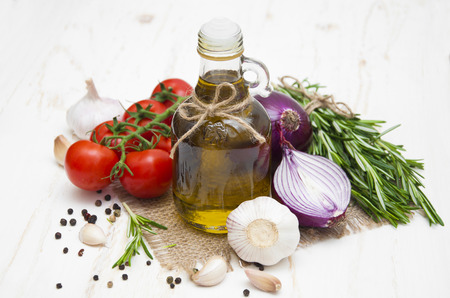 red onions: Olive oil, cherry tomatoes, garlic, red onions and rosemary on a white wooden background