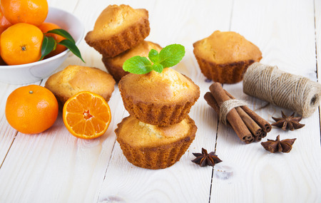 small basket: Fresh homemade cupcakes with tangerines and spices on wooden background