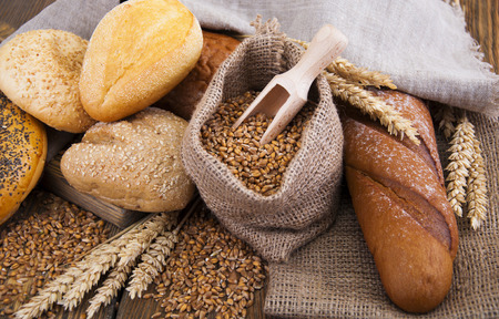 bakery products: Different bread with wheat in a small bag on a wooden background Stock Photo