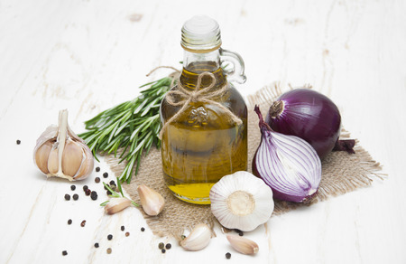 red onions: Olive oil, garlic, red onions and rosemary on a white wooden background Stock Photo