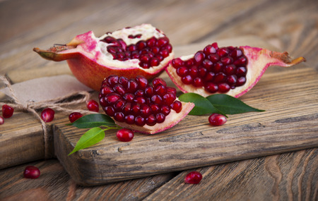 Juicy pomegranate and red grains on wooden background