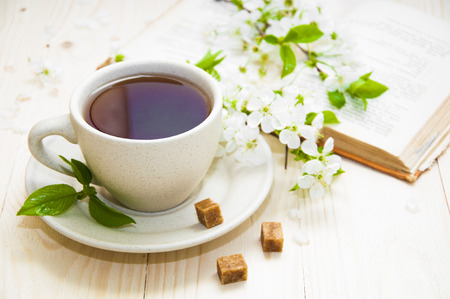 hot spring: A cup of tea with spring flower cherry blossom and old book on a wooden background Stock Photo