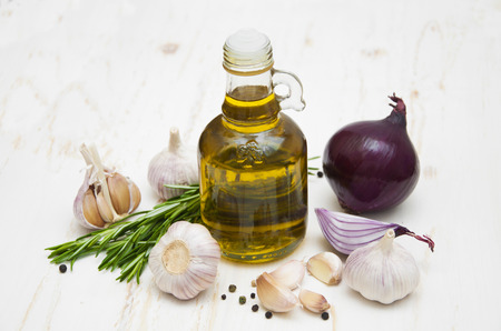 garlic cloves: Olive oil garlic red onions and rosemary on a white wooden background Stock Photo