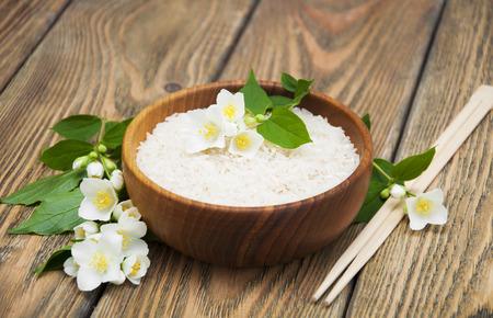 arroz: Placa de madera con arroz jazmín y flores de jazmín en un fondo de madera