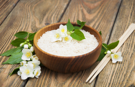 rice: Wooden plate with jasmine rice and jasmine flowers on a wooden background