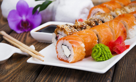 Different Sushi rolls,wasabi and ginger on a plate on wooden background Stock Photo