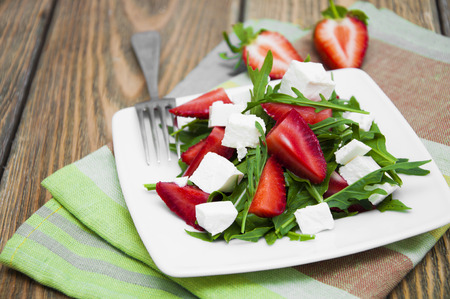 Fresh salad with strawberries, arugula and feta cheese on a wooden table