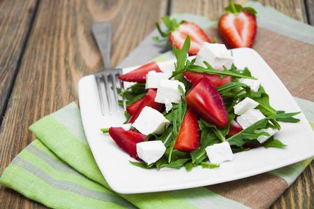 l�gumes vert: Salade fra�che avec des fraises, roquette et fromage feta sur une table en bois Banque d'images