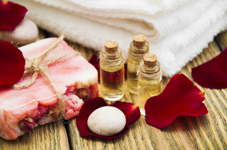 handmade soap: Rose essential oil with handmade soap on wooden background