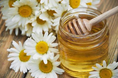 cuchara: Miel fresca primavera con flores de manzanilla en mesa de madera Foto de archivo