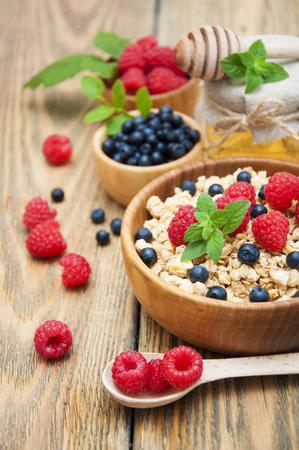 eating breakfast: Breakfast with muesli and raspberries, blueberries, honey on wooden table Stock Photo