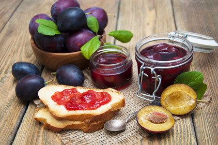 Sandwiches with plum jam. Plum jam in a glass jar with fresh plums on wooden background