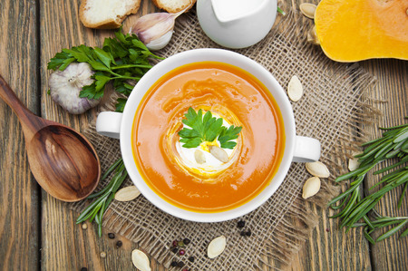 marchew: Zupa dyniowa puree z przyprawami na drewnianym stole Zdjęcie Seryjne