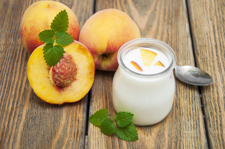 Homemade yogurt with fresh peaches on a wooden background