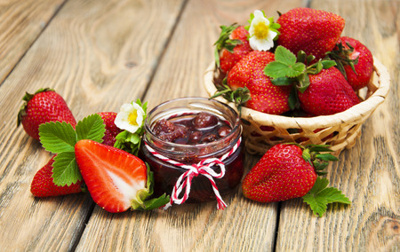 mermelada: Mermelada de fresa fresca en un tarro de fresas en un fondo de madera