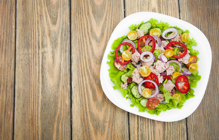 prepared potato: A fresh and colorful tuna salad on a wooden background Stock Photo