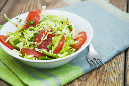 tomate ensalada: Salad with fresh cabbage, tomato, cucumber and herbs on the plate on a table