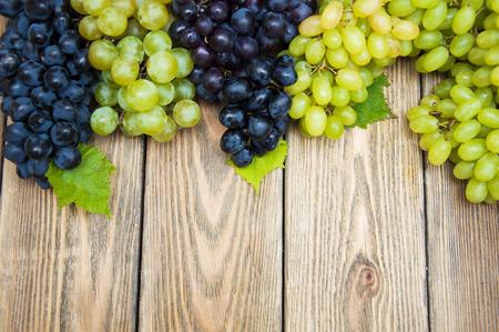 Groene en blauwe druiven op een oude houten backgroun