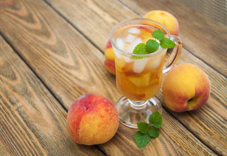 A refreshing cold drink with peach on a wooden table Stock Photo