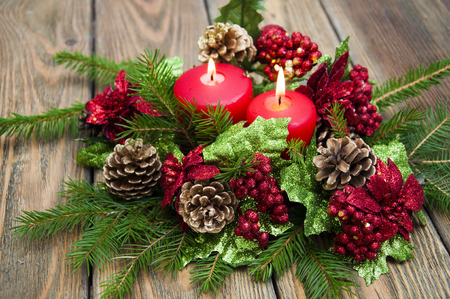 Christmas decoration with red candle on the wooden table. Christmas still life background