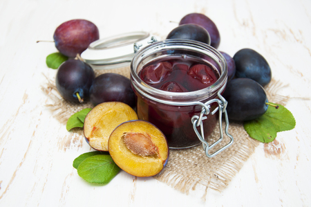 Plum jam in a glass jar with fresh plums on wooden background Banco de Imagens