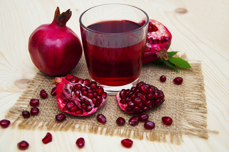 pomegranates: Fresh pomegranate juice in a glass with fruit pomegranates on a wooden background Stock Photo