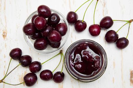 mermelada: Mermelada de cereza con cerezas frescas sobre un fondo de madera