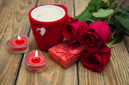 heart gift box: A cup of cappuccino with heart, gift box, candles and red roses on a wooden background Stock Photo