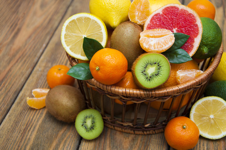 citruses: Fresh juicy citrus fruits in a basket on a wooden background Stock Photo