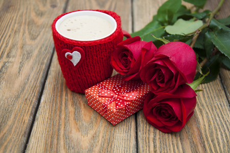heart gift box: A cup of cappuccino with heart, gift box and red roses on a wooden background