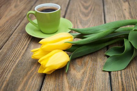 Aromatic coffee with yellow tulips on a wooden background