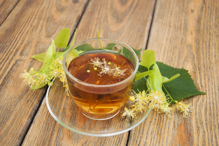 A cup of herbal linden tea with flowers on a wooden background