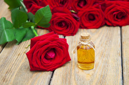 Bottles essence aroma oil with roses and petals on a wooden background. Transparent Little Bottles