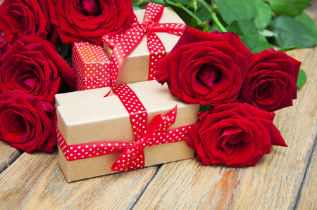 Beautiful bouquet of roses with a gift box on a wooden background 写真素材