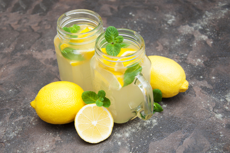 Homemade lemonade with fresh lemon and mint on a stone background