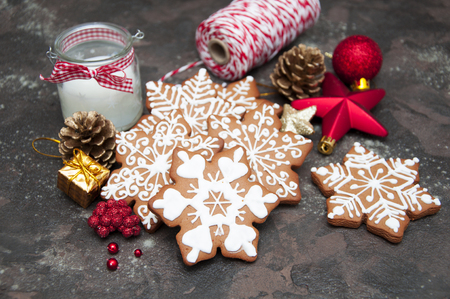 Christmas ginger cookies with christmas baubles on a stone background