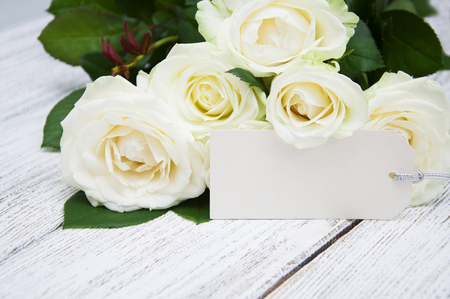 Beautiful bouquet of roses with a greeting card on a wooden background