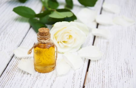 Bottles essence aroma oil with roses and petals on wooden background. Transparent Little Bottles 写真素材