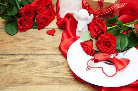 木製のテーブルにフォークとナイフを添えたバレンタインディンのためのテーブルを提供