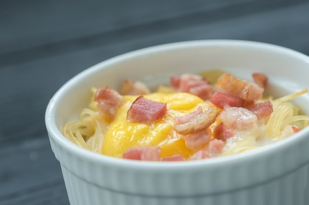 Delicious pasta with egg and bacon served in white bowl