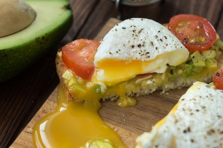 Toast with avocado,poached egg and tomatoes cherry cooked in olive oil Stock Photo