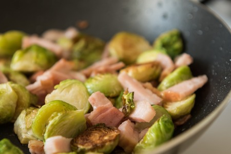 fryingpan: Cooking brussels sprouts with ham in frying-pan Stock Photo