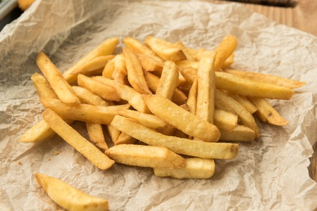 traditionally american: Homemade hot french fries with salt on a paper