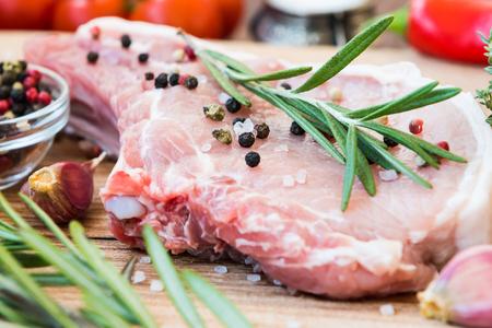 seasonic: Raw meat on the bone with fresh rosemary, thyme, pepper, sea salt and garlic Stock Photo