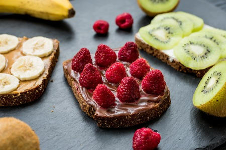 Gluten free toasts with raspberries, bananas and kiwi for breakfast