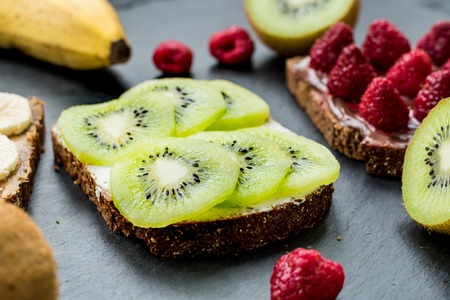 Sweet delicious toasts with raspberries, bananas and kiwi for breakfast Standard-Bild