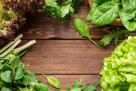 Fresh washed homegrown greens on wooden table Standard-Bild
